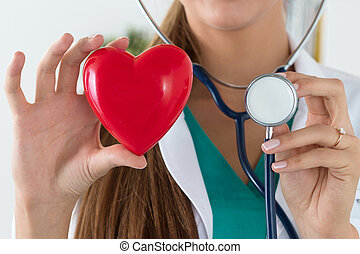 Close-up of female doctor hands holding read heart and...