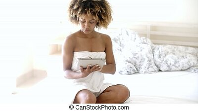 Young Woman Using Tablet On Bed - Relaxed african woman...