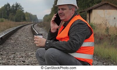 Railway employee drinking coffee and talking on the...