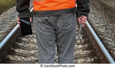 Railway employee with adjustable wrench and tablet PC on...