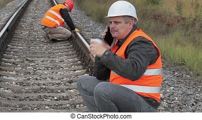 Railway employee talking on the smartphone and drinking...