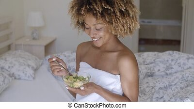 Young Woman On Bed Eating Vegetable Salad - Young african...