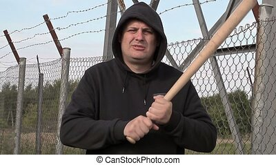 Aggressive man with baseball bat near wire fence