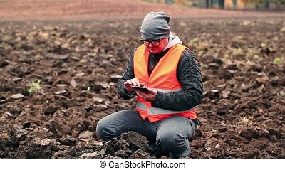 Farmer checking ground on the plowed field