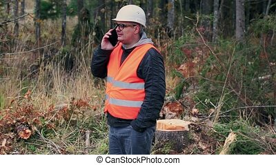 Forest inspector with smartphone in forest