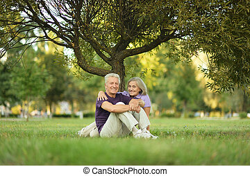 couple sitting on green - Mature couple sitting on green...