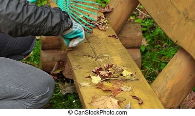 Man collect leaves from the bench in the park