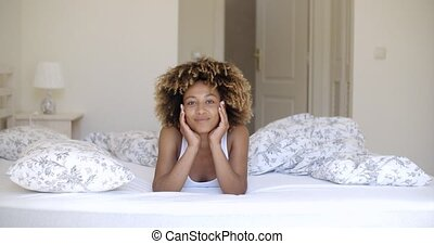 Cute african woman lying on bed and looking at camera. -...
