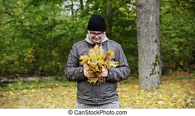 Man throw autumn leaves