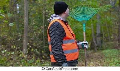 Tired worker with a rake in the park