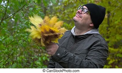 Man throw autumn leaves in the park