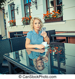 beautiful young girl resting in a cafe. attractive blond model sitting with a cup of coffee in an outdoor cafe of the European city and talking on the phone