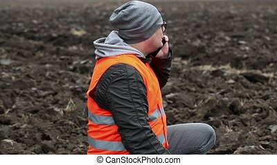 Farmer with with smartphone on the plowed field
