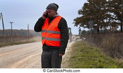Engineer with smartphone in road repairs