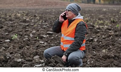 Farmer with smartphone showing gestures on the plowed field
