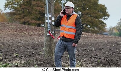 Electrical engineer with cell phone at outdoor near high...