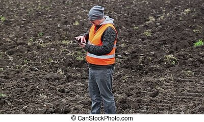 Farmer using tablet PC on the plowed field