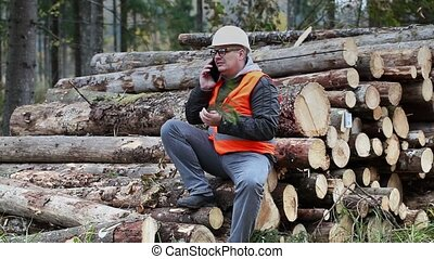 Forest officer talking on smartphone in the woods