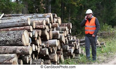 Forest officer with smartphone near logs
