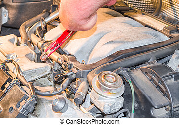 Car engine Service - Hand of an auto mechanic in the engine...