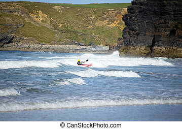 kayaker riding waves at ballybunion - bright winter view of...