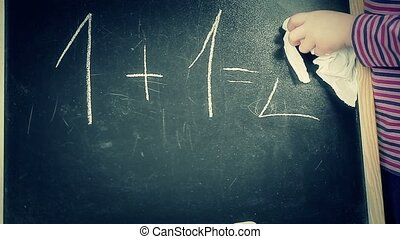 Little girl clear math task from the blackboard