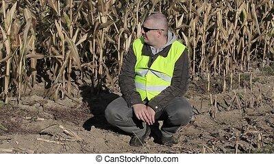 Farmer on cold corn field in autumn