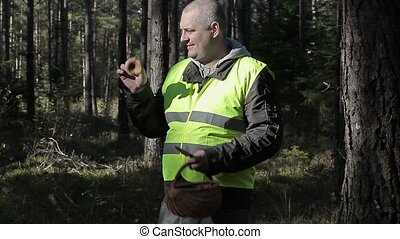 Man with mushroom and basket in forest in autumn