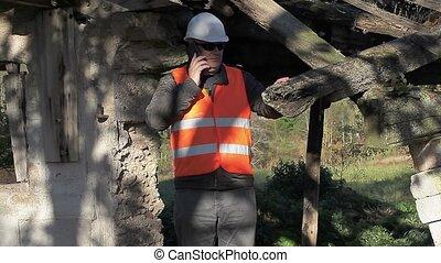 Building inspector talking on smart phone - Building...
