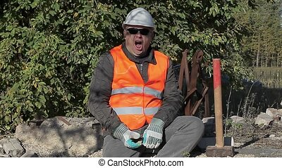 Tired construction worker struggling with sleep near a pile...