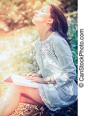 Thoughtful Woman Sitting on Grasses at the Garden -...