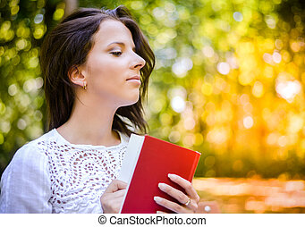Thoughtful Woman Holding a Book at the Park - Close up...