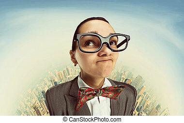Funny dreaming nerd girl in glasses against sky