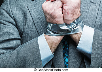 Businessman with hands covered by masking tape, studio shoot