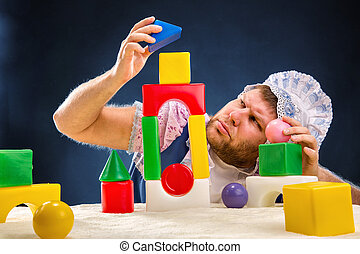 Man weared as baby playing with toy bricks