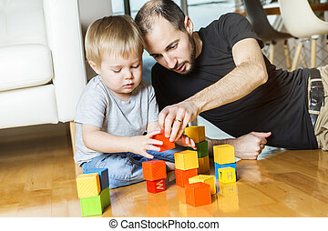 father play block with his son at home - A father play block...