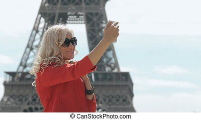 Attractive blonde in sunglasses doing selfie against the backdrop of the Eiffel Tower in Paris