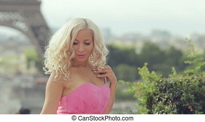 Beautiful girl in a pink festive dress sitting on a background of the Eiffel Tower