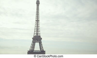 Dreamy girl in the lush pink long dress looking at the Eiffel Tower in Paris