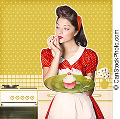 Young housewife holding sweet cupcake in her hands.Retro...