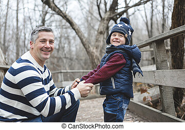 happy father and son having fun in park at the end of...