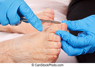 Foot care - doctor hand examining an elderly patient's foot