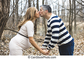 Beautiful outdoor pregnant couple portrait in autumn nature...