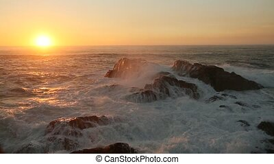 Ocean surf on the rocky shore during a wonderful sunset.