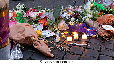 Flowers and lit candles in front of the French Embassy in...