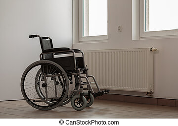 Photo of empty wheelchair in hospital room