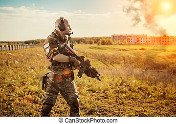 Soldier with the rifle is looking at the smoke under the city. Ruined buildings on the background.