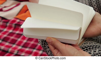 Flipping Blank Pages - Young woman flipping blank pages