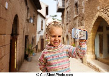 Little girl doing selfie in the street