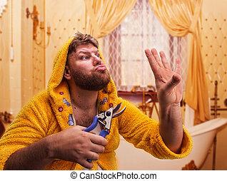 Strange man looks at his nails